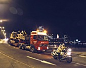 Night transportation of mobile crawler crane on low loader with Police escort. London, United Kingdom.