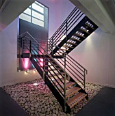 Modern steel staircase lit by coloured spotlights.