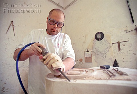 Stonemason using a pneumatic chisel in workshop
