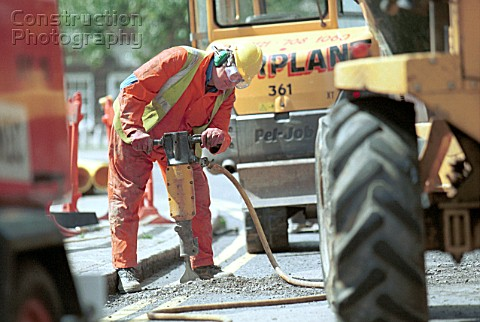 Public Utilities Man working on a road with a jack hammer