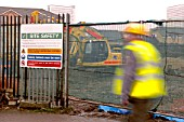 Worker walking past temporary site fencing showing safety sign.
