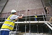 Two construction workers throwing bricks, United Kingdom.