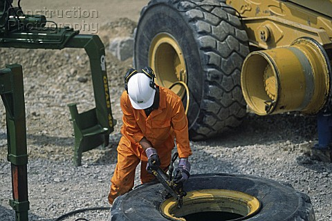 A008-00473: Mechanic changing tyre on heavy duty articul ...
