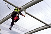 Abseiler checking the steel structure of Kings Hospital roof, Camberwell, London