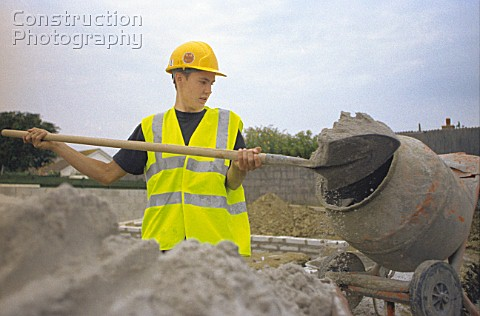 Young builder mixing sand and cement in a portable concrete mixer
