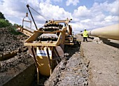 Excavating pipe trench using trenching machine. Lincolnshire gas pipeline works, United Kingdom.