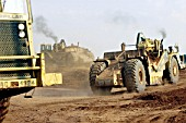Caterpillar scrapers working on earthworks for the M6 Toll road around northern Birmingham, United Kingdom.
