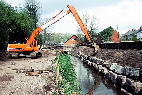 Long reach excavator finishing embankment face on a drainage channel for flood protection in Newport