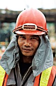 Worker on site in Singapore with sun protection cloth under helmet