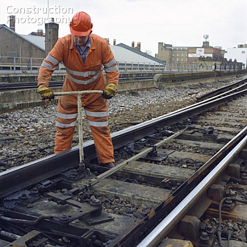 Rail worker adjusting points on railway line