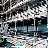 Hazardous building site with health and safety non compliant scaffolding