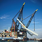 Two cranes transport pylons for the Erasmus Bridge, Rotterdam, Holland. The bridge is nicknamed the Swan and was designed by UN Studio