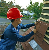 Young roofer replacing tiles on a house