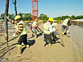 Construction workers laying down concrete