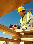 Man planing wood on construction site