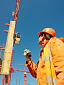 Man looking up and talking to crane driver on walkie talkie, low angle