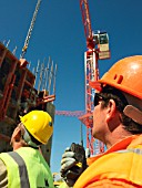 Man holding walkie talkie, positioning glass fibre reinforced (GRC) concrete panel