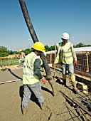 Men pouring concrete on to reinforced steel bar