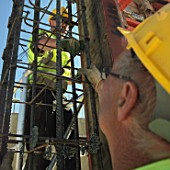 Men working on reinforced steel bar structure for reinforced concrete foundations