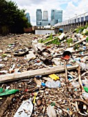 Dumped rubbish and rubble with Canary Wharf in Background, London, UK
