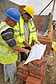 Bricklayer and site foreman looking at plans on a house building site, England, UK.