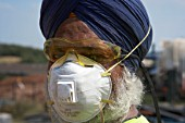 Sikh worker wearing turban and protection mask and goggles, UK. Sikh workers are allowed not to wear hard hat on site because of their religious beliefs.