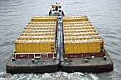 Container barge on River Thames, London, UK