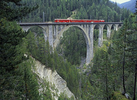 Local train of Rhaetian railway crossing viaduct  Swiss alps  canton of Grisons  Switzerland