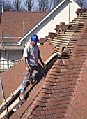 Roof tiler fixing hip bonnet tiles to roof of detached house.