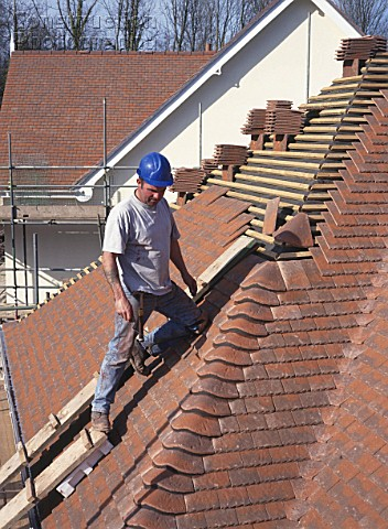 Roof tiler fixing hip bonnet tiles to roof of detached house