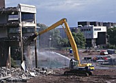 Demolition of reinforced concrete frame buildings in Cwmbran for redevelopment of town centre.  Water jet played over the falling concrete dampens down dust.
