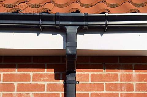 Drainage Pipe On Brick House With Tile Roofing