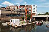 Floating platform with excavator and barge on the Lower Lea canal regeneration scheme, East London, UK