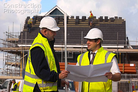 Construction manager and Foreman looking at plans on site