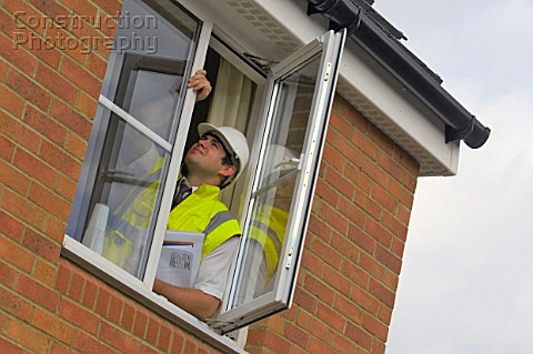 Construction manager inspecting windows in a new build house