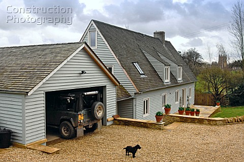 A timber clad house with a gravel drive Gloucestershire UK