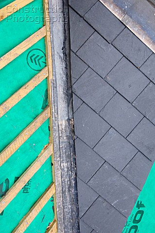Section of slate roof under construction showing the breathable roofing felt with lead flashing vall