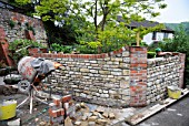 Building a garden wall with cotswold stone and cement mortar with reclaimed red brick pillars and coping UK