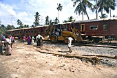 Reconstruction of the railway line demolished after the Tsunami, Village of Peraliya, Sri Lanka, February 2005. Derailed Remains of the Queen of the Sea engine no.59 and its eight carriages on the Colombo - Galle express route. The worlds worst ever train disaster