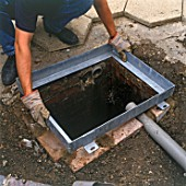 Installing a manhole cover over the drain.
