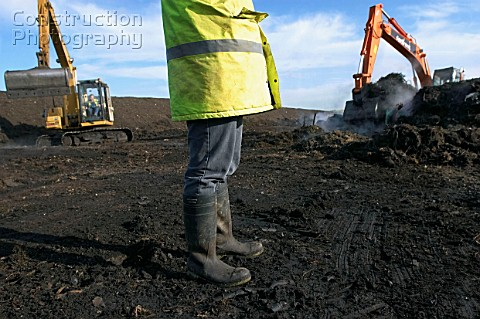 Legs of site warden with tracked excavator on landfill