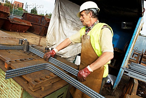 Concrete reinforcement steel rebar cut and bent factory Worker bending steel rods