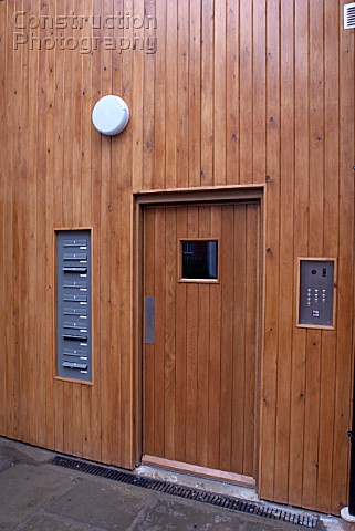 Door with names on buzzers and wooden cladding