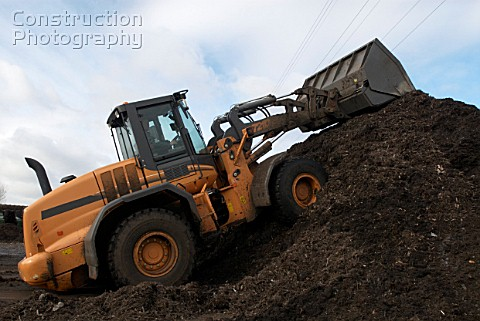 Front loader on compost heap at recycling centre