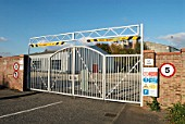 Barrier gate at with a height restriction at an entrance to a factory, Stowmarket, UK