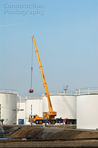 A generator hoisted by a mobile crane onto a site at Harwich Refinery Suffolk UK
