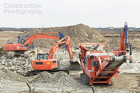 Excavator clearing a demolished site with an aggregate Crusher to make way for a paper recycling pla
