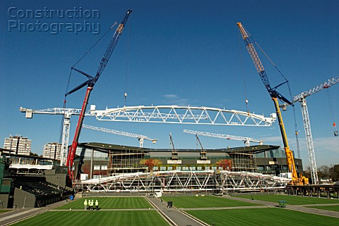 Two cranes work in tandem to lift roof trusses on to fixed roof of Centre Court All England Lawn Ten