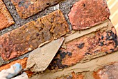 Close up of bricklayers trowel repointing a chimney stack