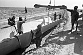 Workers laying concrete chutes at the construction of irrigation canals Tajikistan, USSR, 1985